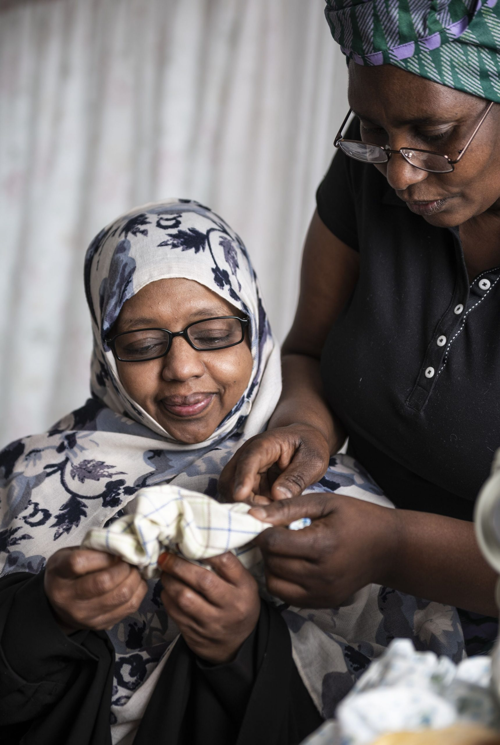photo of two refugee women working together at sewing machine